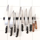 Set of knives on magnetic holder — Stock Photo