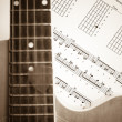 Acoustic Guitar on music note sheet — Stock Photo