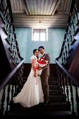 Bride and groom standing at ladder indoor of old building — Stock Photo