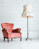 Armchair with desk lamp in vintage room — Stock Photo