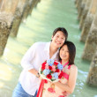 Portrait of smiling couples under the pier on the beach — Stok fotoğraf