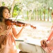 Woman playing violin with her boyfriend — Stock Photo