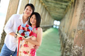 Portrait of attractive couples under the pier on the beach — Stock Photo