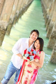 Portrait of smiling couples under the pier on the beach — Stock Photo
