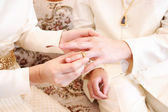 Bride putting a wedding ring on groom 's finger — Stock Photo