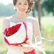Beautiful bride outdoors with rose bouquet — Stok fotoğraf