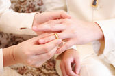 Bride putting a wedding ring on groom 's finger, close up — Foto de Stock
