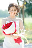 Beautiful bride outdoors with rose bouquet — Stock Photo