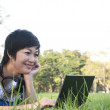 Asian lady using computer in a park — Stock Photo