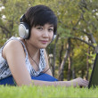 Beautiful asian woman listening music in the park — Stock Photo