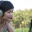 Stock Photo: Beautiful asian woman listening music in the park