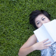 Young woman reading a book in the park — Stock Photo #12513700