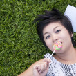 Young woman eating a candy in the park — 图库照片