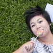 Young woman eating a candy in the park — Stock Photo