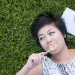 Young woman eating a candy in the park - Stock Photo
