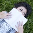 Stock Photo: Young woman reading a book in the field