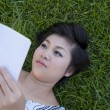 Stock Photo: Young womreading book in field