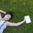 Young woman reading a book in the field — Stock Photo #12515539