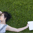 Young woman reading a book in the field — Stock Photo