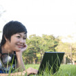 Asian lady using computer in a field — Stock Photo #12517513
