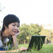 Asian lady using computer in a field — Stock Photo #12517661