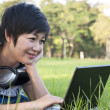 Asian lady using computer in a field — Stock Photo