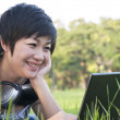 Asian lady using computer in a field — Stock Photo #12518058