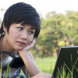 Asian lady using computer in a field — Stock Photo #12518131