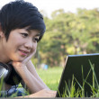 Asian lady using computer in a field — Stock Photo #12518291