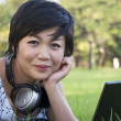 Stock Photo: Asian lady using computer in a field