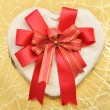 Heart-shaped box with bow on gold background — Stok Fotoğraf #12520719