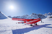 Red plane on glacier — Stock Photo