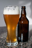 Wheat beer glass and brown bottle — Stock Photo