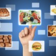 Woman hand uses touch screen interface with food - Zdjęcie stockowe