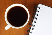Cup of coffee with notepad — Stock Photo