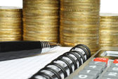 Stationery with stack of coins — Stock Photo