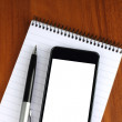 Smart phone, pen and notepad - Stock Photo