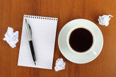 Cup of coffee with notepad, pen and crumpled paper — Stock Photo