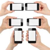 Manos sosteniendo los teléfonos inteligentes — Foto de Stock