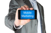 Businessman holds smart phone with mobile marketing words — Stock fotografie