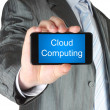 Foto Stock: Businessman holds smart phone with cloud computing words
