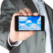 图库照片: Businessman holds smart phone with cloud computing concept