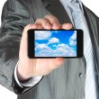 Businessman holds smart phone with cloud computing concept — Stock fotografie