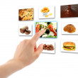 Woman hand uses touch screen interface with food — Stock Photo