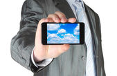 Uomo d'affari tiene smart phone con il concetto di cloud computing — Foto Stock