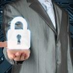 Businessman with lock on dark circuit board background — Stock Photo #31221933