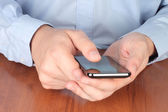 Businessman touching smart phone — Stock Photo