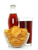 Bottle and glass of cola with potato chips — Photo