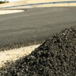 Asphalt and asphalting the road - Stock Photo