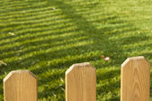 Wooden decorative fence and green garden — Stock Photo